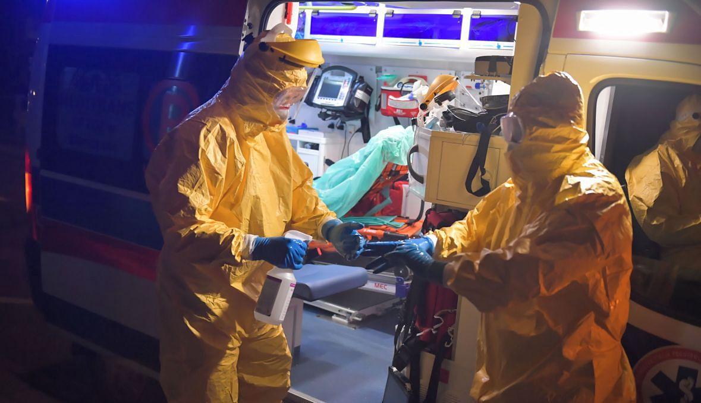 Pogotowie ratunkowe transportuje osobę podejrzaną o zakażenie wirusem Covid-19 (zdjęcie ilustracyjne. Mężczyźni z fotografii nie występują w tekście)
