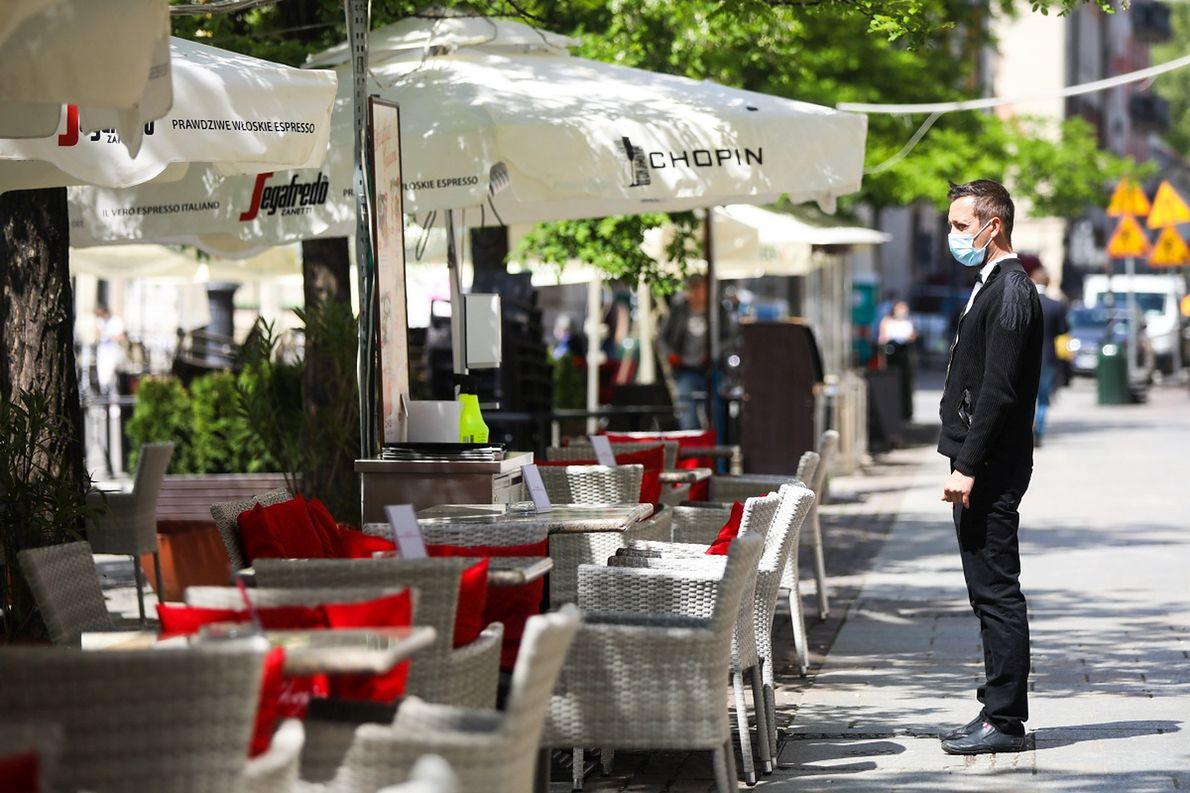 Kelner oczekuje na klientów przed restauracją w Krakowie