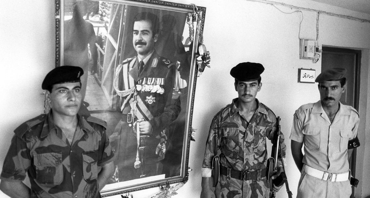 Iraccy żołnierze pełnią wartę przy obrazie Husajna. Bagdad, rok 1990