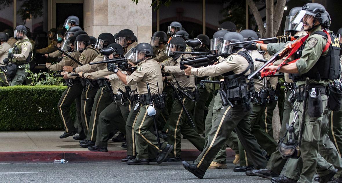 Policjanci ruszają w kierunku ludzi, którzy odmówili rozproszenia się po godzinie policyjnej