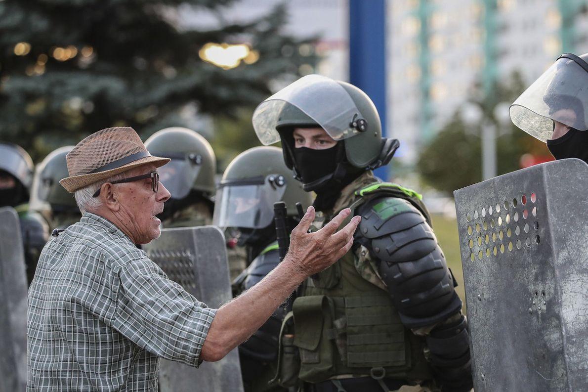 Starszy mężczyzna dyskutuje z policją podczas protestów w Mińsku