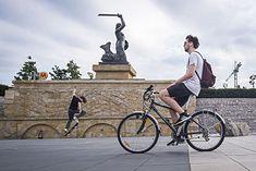 Rowerzysta na tle pomnika warszawskiej Syrenki