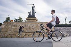 Na zdjęciu: rowerzysta na tle pomnika warszawskiej Syrenki