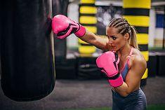 Kobieta uderzająca w worek bokserski