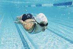 Kobieta w czepku pływająca pod wodą na basenie
