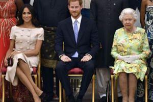 """Księżna Meghan złamała protokół: """"Siedziała ze skrzyżowanymi nogami i próbowała złapać Harry'ego za rękę"""" (WIDEO)"""