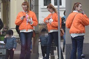 Kasia Burzyńska wpatrzona w telefon na spacerze z synem