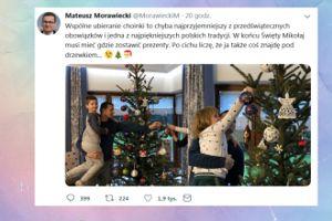 Premier Morawiecki z wyrośniętym synem na ręku ubiera choinkę