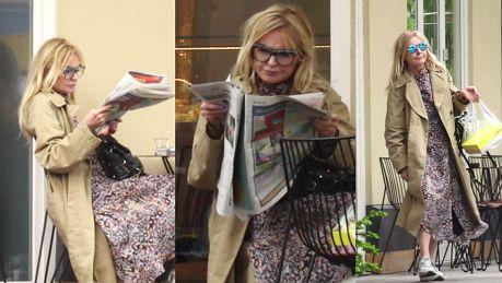 Monika Olejnik w zwiewnej sukni przegląda gazetę