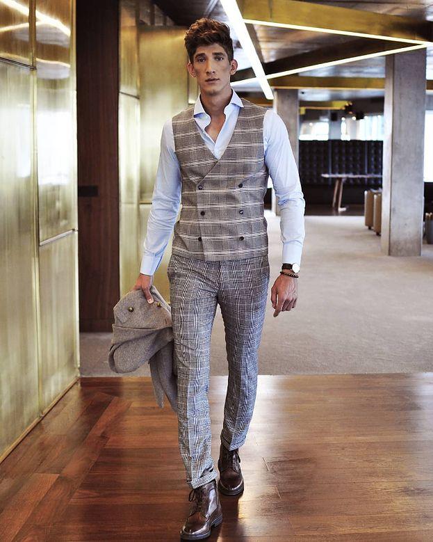 d1a092a91a8be ... Model Michał Baryza zdecydował się połączyć szarą kamizelkę w kratę z  dopasowanymi spodniami o podobnym wzorze oraz białą koszulą.