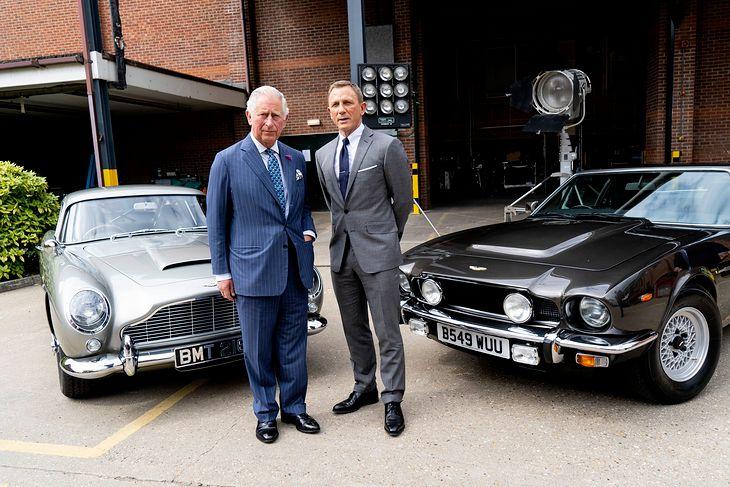 Daniel Craig i Książę Karol przy filmowych Astonach Martinach DB5 i V8 Vantage