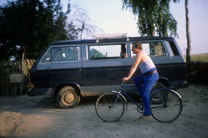 Lech Wałęsa jedzie rowerem na tle Volkswagena, który aktualnie jest do sprzedania