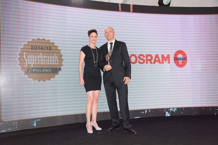 Janusz Mitko, dyrektor działu marketingu firmy OSRAM odbiera statuetkę z rąk Moniki Kowalewskiej, dyrektor projektu Superbrands Polska.