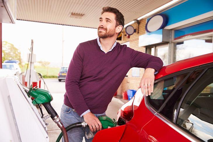 Mężczyzna tankujący samochód z Shutterstock