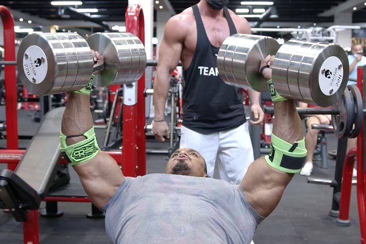 Larry Wheels wyciskający hantle o wadze 100 kg