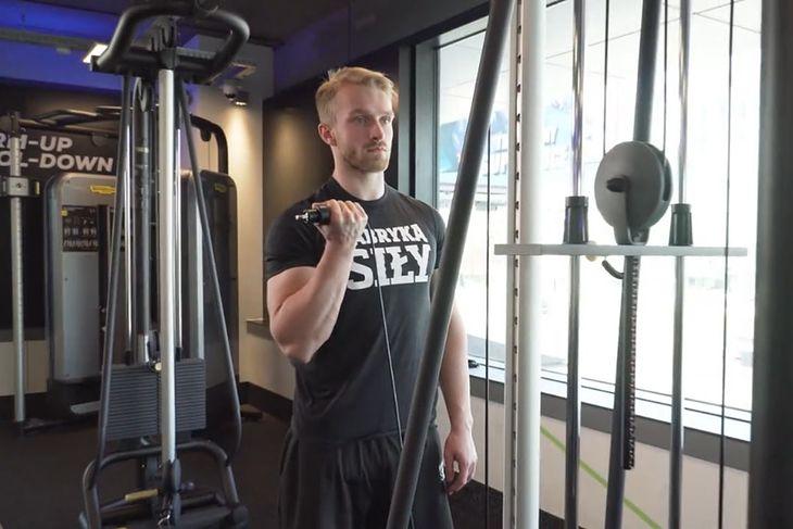 Mateusz Matłosz, trener personalny i ekspert Fabryki Siły, demonstruje ćwiczenie na biceps
