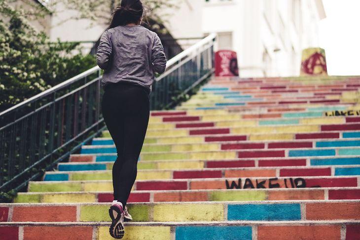 Na zdjęciu: kobieta wbiegająca po schodach