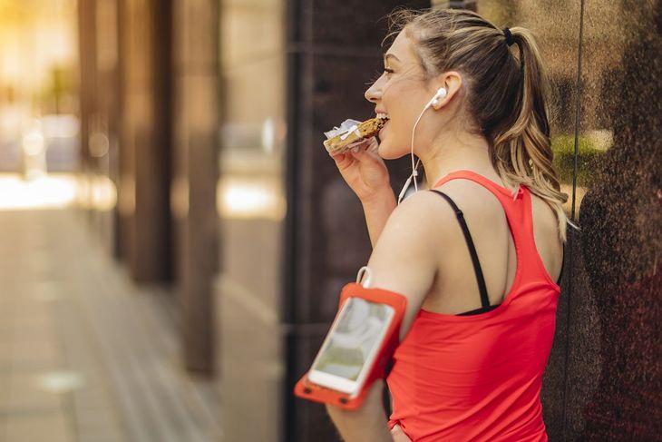 Biegaczka zjada batonik przed treningiem