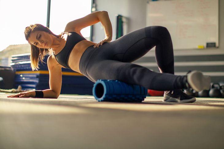 Kobieta rozmasowuje mięśnie przy pomocy rollera z wypustkami
