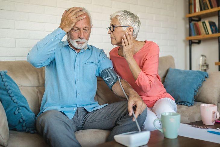 Mężczyzna z bólem głowy wykonuje pomiar ciśnienia tętniczego
