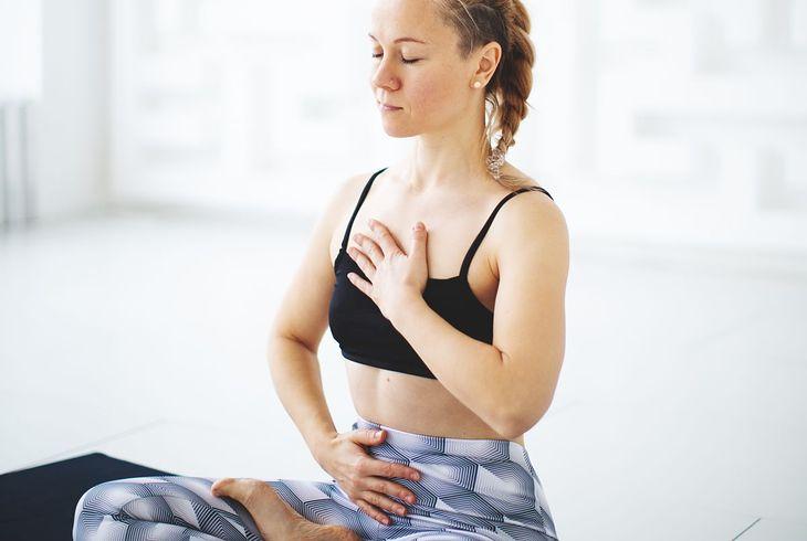 Kobieta wykonująca ćwiczenie oddechowe (zdjęcie ilustracyjne)