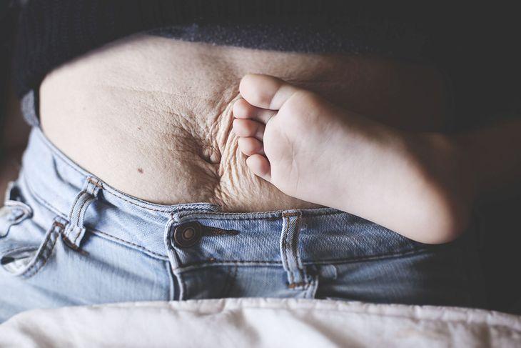 Brzuch kobiety po porodzie i stopa jej dziecka