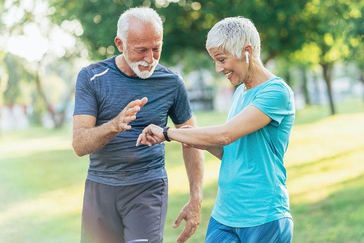 Para seniorów podczas spaceru, kobieta używa krokomierza