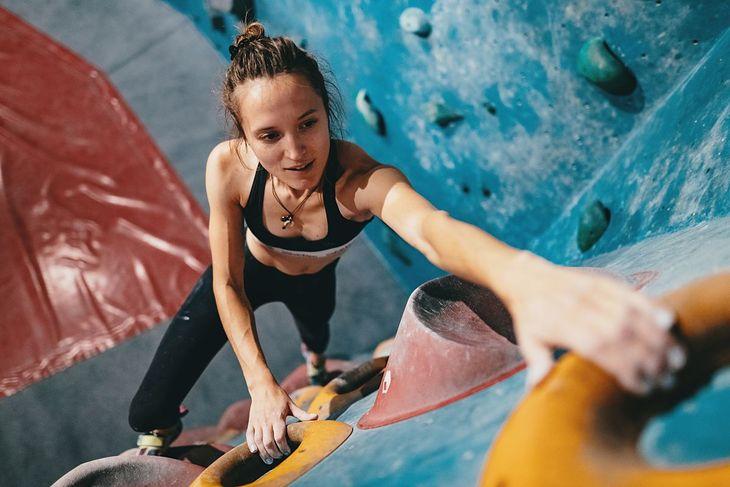 Kobieta uprawiająca bouldering na ściance