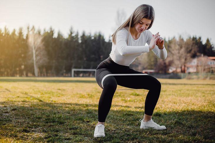 Kobieta wykonująca ćwiczenie z gumą (zdjęcie ilustracyjne)