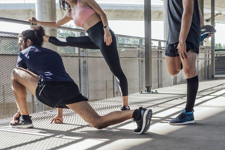 Grupa biegaczy wykonująca rozgrzewkę