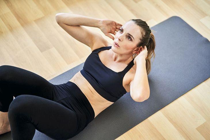 Kobieta ćwicząca brzuszki na macie treningowej