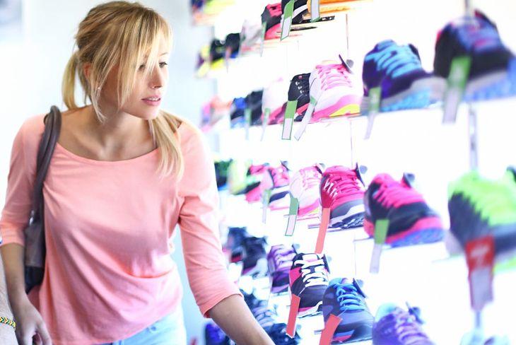 Kobieta wybiera buty do biegania damskie (zdjęcie ilustracyjne)