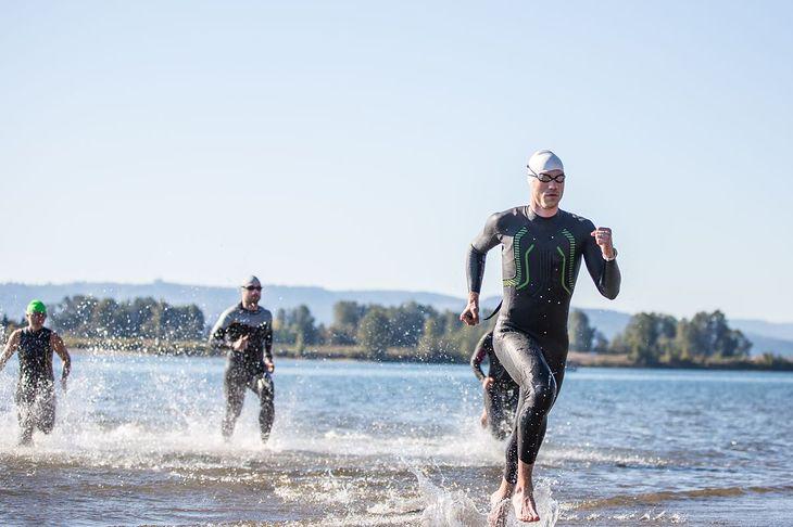 Triathlon składa się z trzech konkurencji. Na zdjęciu: zawodnicy wybiegają z wody po pływaniu