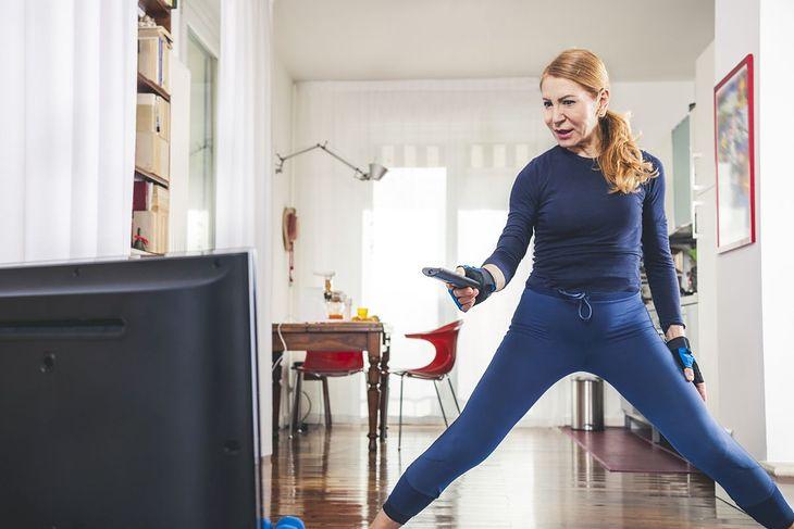Na zdjęciu: kobieta przygotowująca się do ćwiczeń przed telewizorem