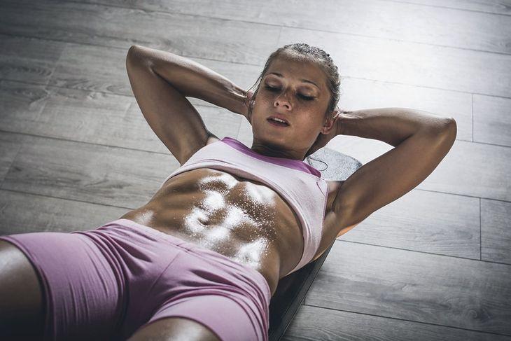 Kobieta wykonuje ćwiczenia na mięśnie brzucha (zdjęcie ilustracyjne)