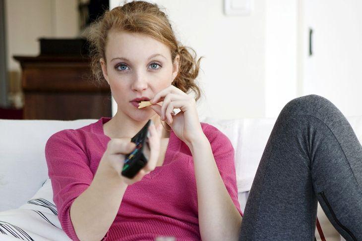 Kobieta podjada podczas oglądania TV