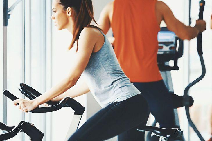 Na pierwszym planie kobieta trenująca na rowerku, w tle mężczyzna na orbitreku