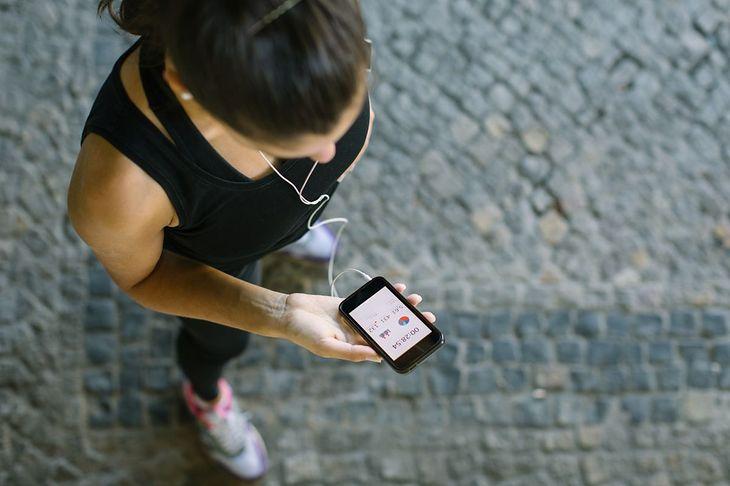 Kobieta przegląda aplikację do biegania (zdjęcie ilustracyjne)