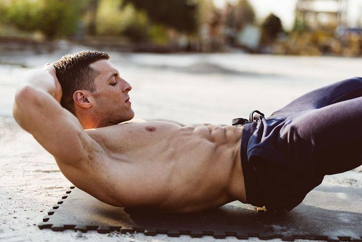 Na zdjęciu: mężczyzna wykonujący ćwiczenia na mięśnie brzucha