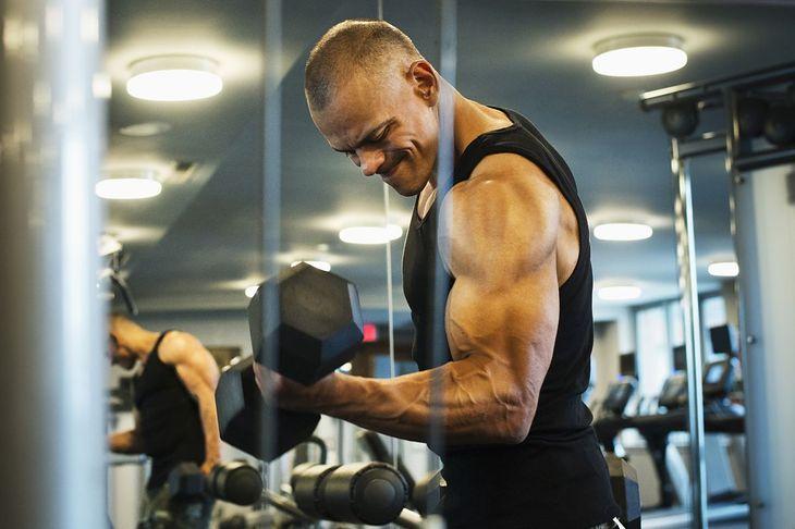 Mężczyzna wykonujący ćwiczenia na biceps (zdjęcie ilustracyjne)