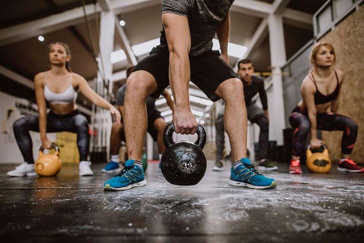 Na zdjęciu: grupa trenująca crossfit, ćwiczenia z kettlebells