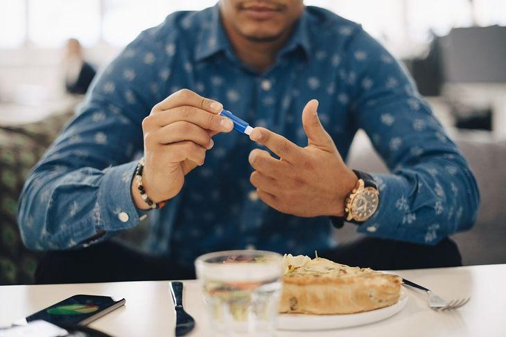 Mężczyzna sprawdzający poziom cukru we krwi