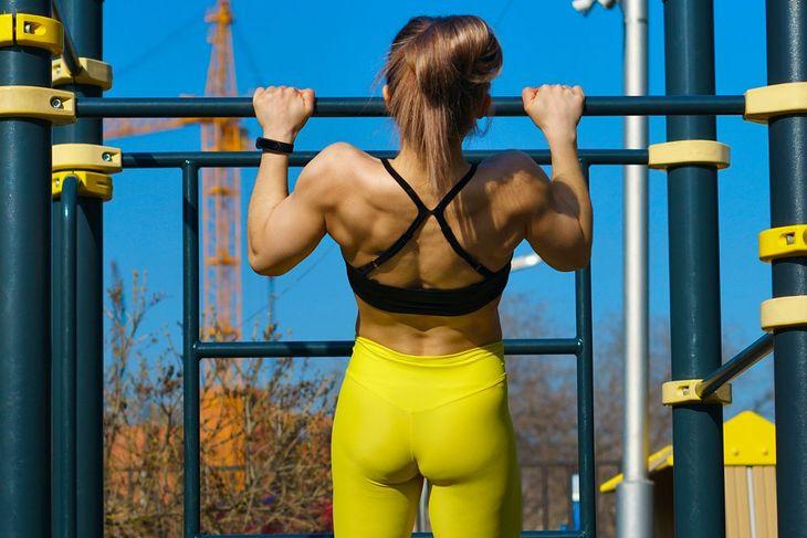 Kobieta podciągająca się na drążku nachwytem