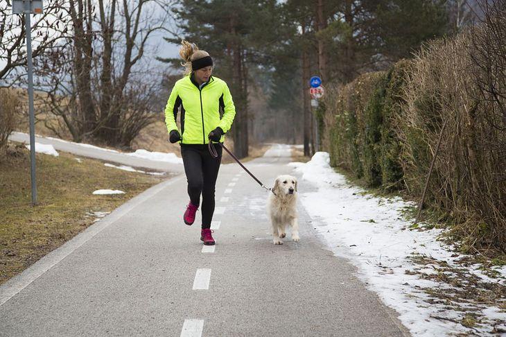 Kobieta biegająca z psem na smyczy