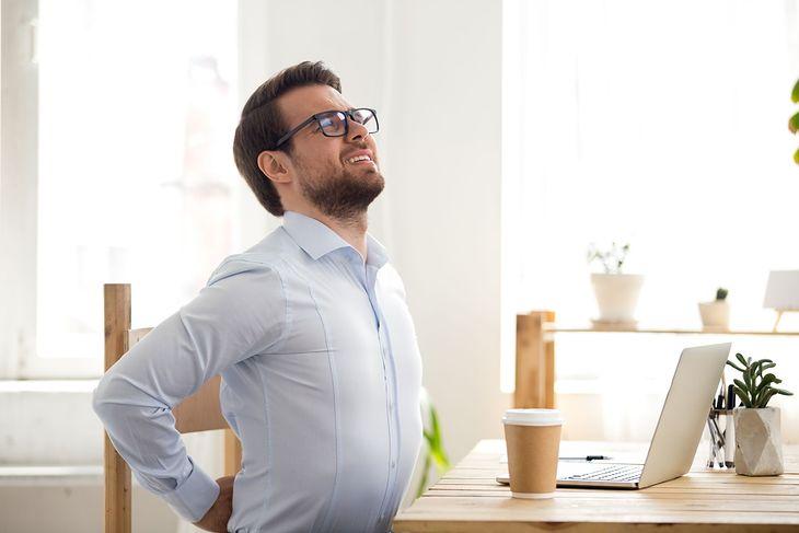 Mężczyzna siedzący przy laptopie, uskarżający się na ból kręgosłupa
