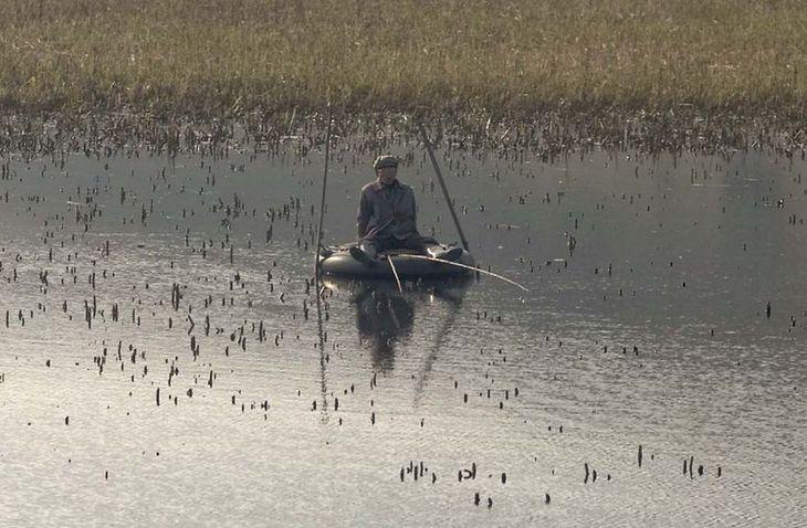 Rybak używa opony zamiast łodzi.