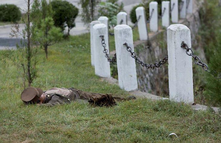 Żołnierz śpi na trawie.