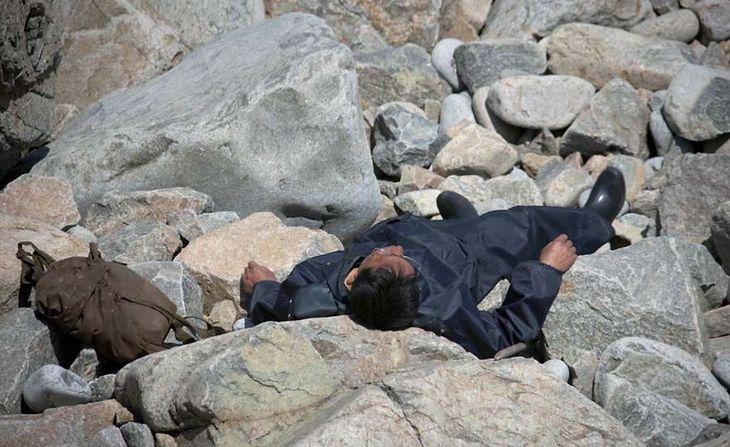 Mężczyzna odpoczywa na kamieniach. Przewodnik prosił o skasowanie zdjęcia, bo bał się, że zachodnie media stwierdzą, że mężczyzna nie żyje. Żył i po prostu odpoczywał.