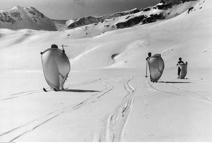 Narciarze podczas jazdy na nartach z przytwierdzonym żaglem na zamarzniętym jeziorze w Dolinie Pięciu Stawów w Tatrach. 1938 r.