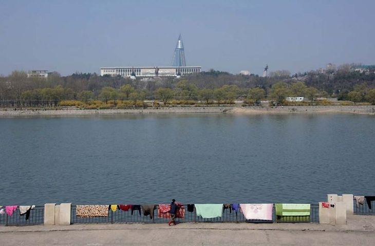 Ludzie suszą dywany nad rzeką.